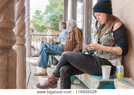 Three People Sitting Outside A Cafe.