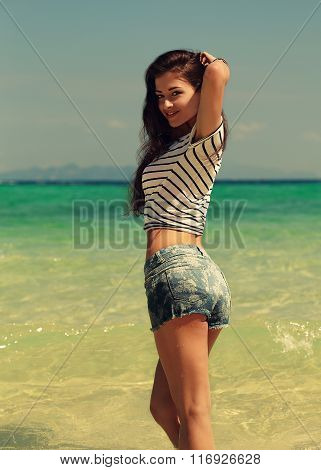 Beautiful Smiling Woman Posing On Sea Background In Blue Shorts And Top