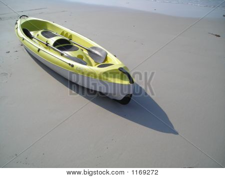 Single Yellow Canoe Lying On Beach