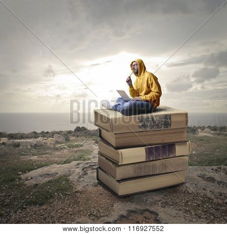 Creative man on a pile of books
