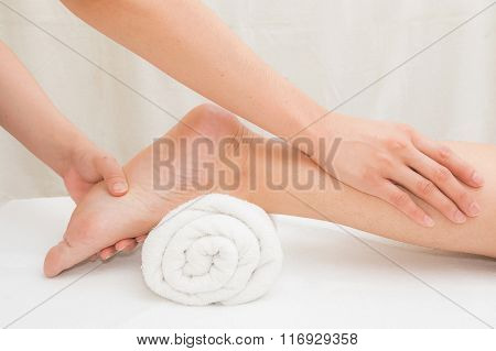 Therapist doing  massage on woman leg  in day spa
