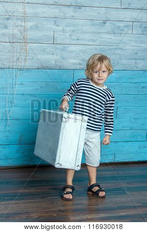 child is carrying a suitcase