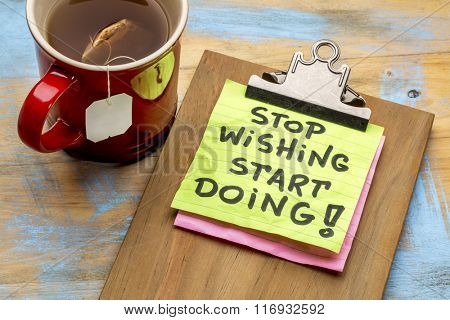 stop wishing, start doing motivational - a sticky note on a clipboard  against grunge wood  grunge wood table