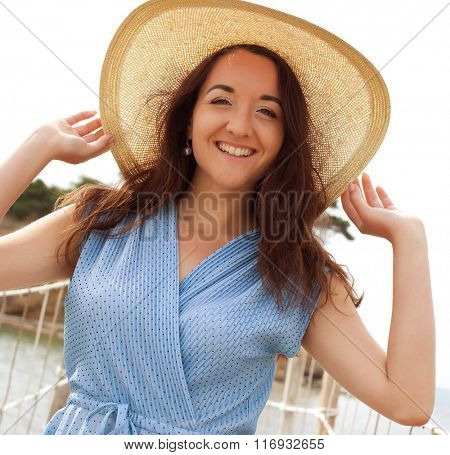Young woman with summer hat posing on the bridge
