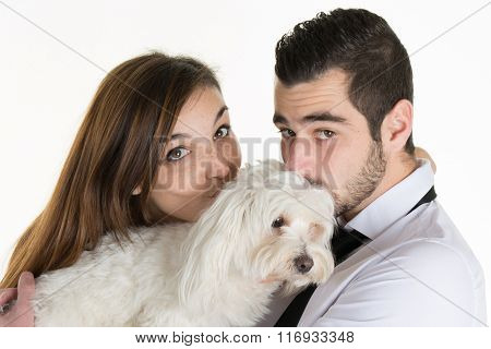 Happy Couple Kissing Their White Dog On Couch At Home