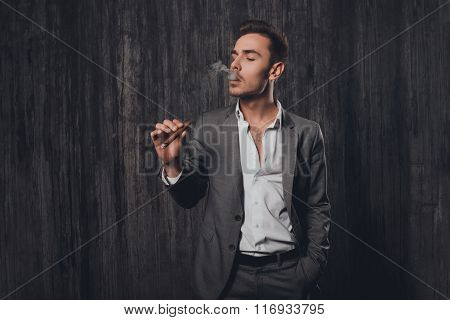 Handome Brutal Man In Suit On The Grey Background Smoking A Cigar