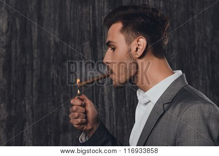 Handome Brutal Man In Suit On The Grey Background Lighting A Cigar