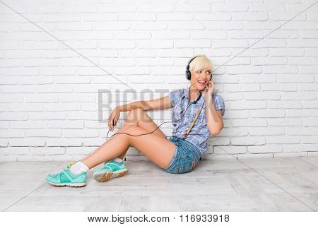 Happy Girl Sitting On The Floor And Listening To Music On Headphones