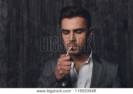 Handome Brutal Man In Suit On The Grey Background Lighting A Cigarette