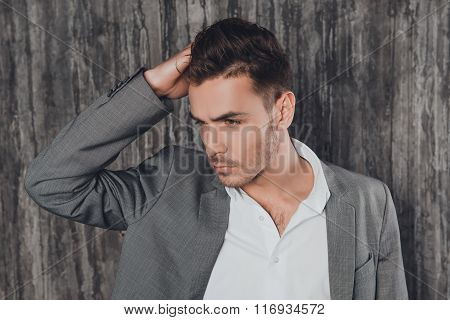 Attractive Man In Suit On The Grey Background Touching Hair