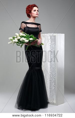 Beautiful sexual redheaded girl in evening dress   with a bouquet of white tulips on a gray background
