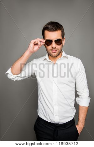 Photo Of Serious Man In Spectacles Holding Hand In Pocket And Touching Spectacles