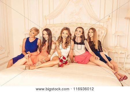 Bridesmaids Sitting On A Luxury Bed And Smiling
