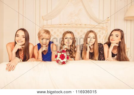 Young Girls Celebrate A Bachelorette Party Of Bride. Bridesmaids Lying On Bed