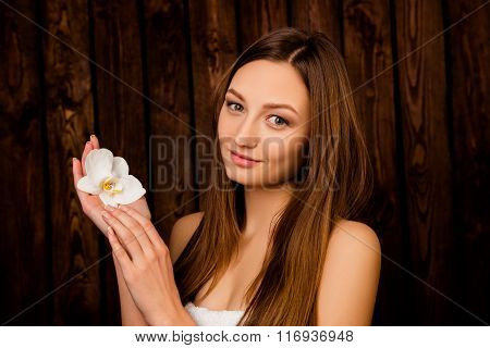 Portrait Of Pretty Girl Holding An Orchid In Her Hands