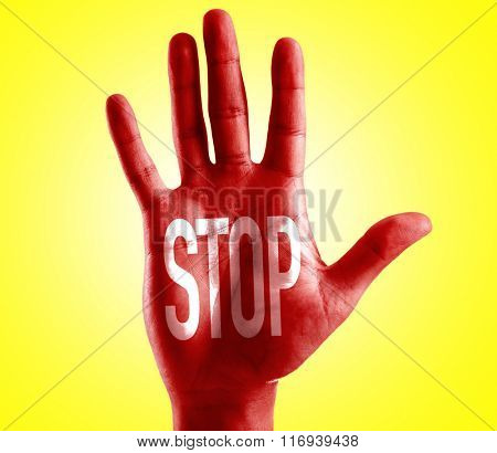 STOP written on hand with yellow background