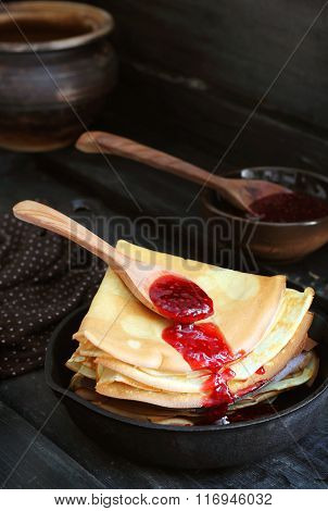 Stack Of Pancakes With Raspberry Sauce In A Cast Iron Skillet