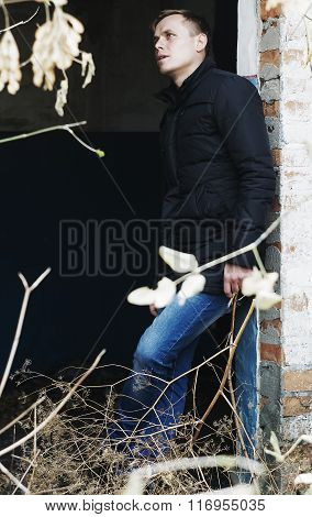 Young Man Stands Against The Wall Of An Abandoned Building