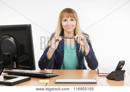 Secretary Girl Sits At A Table And Holding Pen In The Hands
