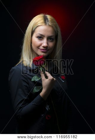 Portrait Of A Beautiful Blonde Girl With A Red Rose In Her Hand Isolated