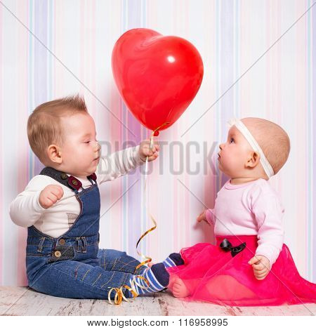 Baby boy giving a heart balloon to the girl on valentines day