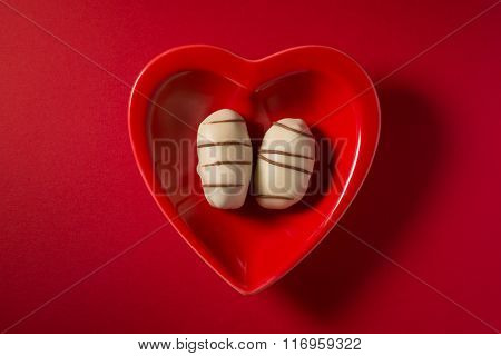 A pair of date chocolates in a red heart shaped dish. Arabic valentines day concept. View from top.