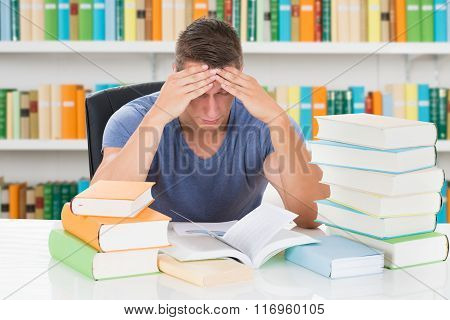 Tensed University Student Sitting In Library