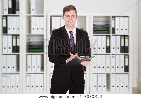 Happy Businessman Holding Clipboard