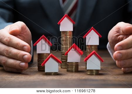 Businessman Covering House Models On Stacked Coins