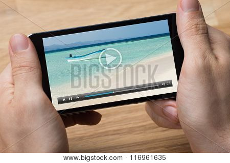 Man Playing Video On Smartphone At Desk
