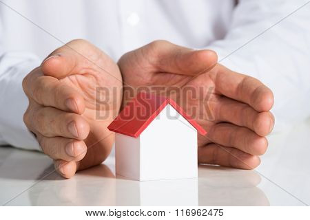 Businessman Protecting House Model At Office Desk