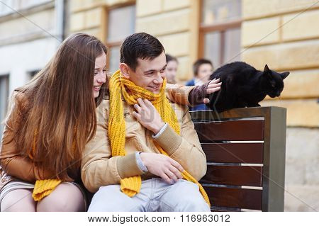 Happy Young Couple With A Cat On A Bench In City