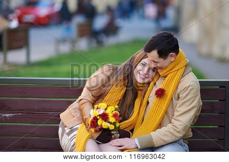 Love Couple Sitting On A Bench With A Bouquet Of Flowers