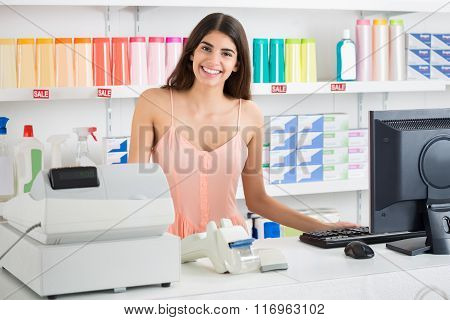 Saleswoman Standing At Cash Register In Supermarket