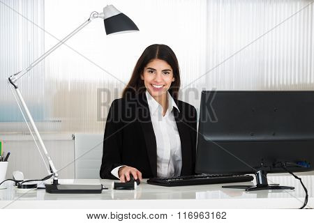 Smiling Businesswoman Using Computer At Desk In Office