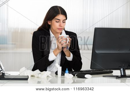 Sick Businesswoman Holding Cap Of Tee At Desk In Office
