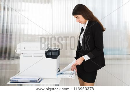 Young Businesswoman Inserting Papers In Photocopy Machine