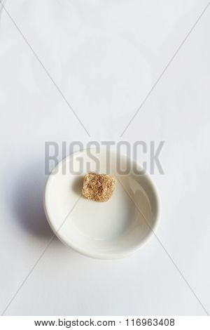 Single Sugar Cube Left In A Small Bowl On White Background