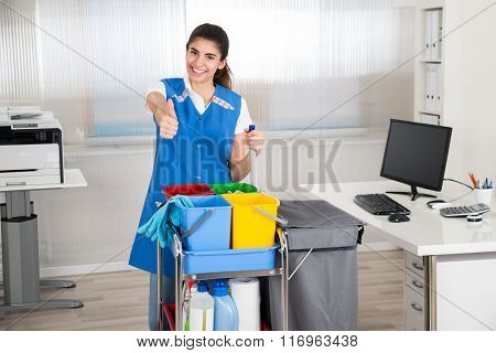 Janitor With Cleaning Equipment Showing Thumbs Up In Office