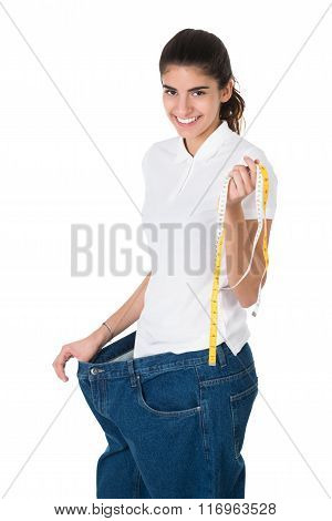 Smiling Woman With Tape Measure Showing Her Old Jeans