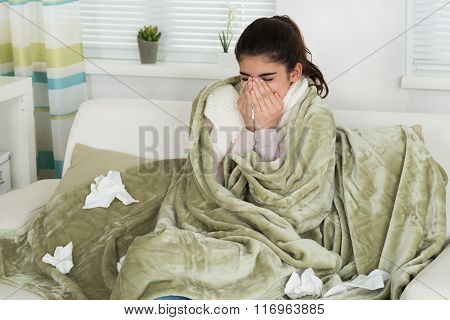 Sick Woman Blowing Nose On Sofa At Home