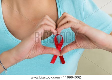 Woman Making Heart Shape In Front Of Aids Awareness Ribbon