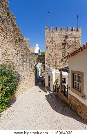Obidos, Portugal. Albarra Tower, Castle Walls and typical street. Obidos is a medieval town still inside castle walls, and very popular among tourists.