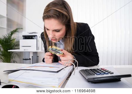 Businesswoman Examining Invoice With Magnifying Glass