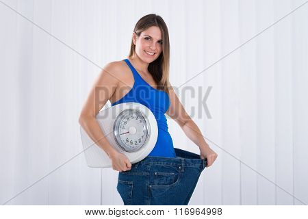 Woman With Weighing Machine Wearing Big Jeans