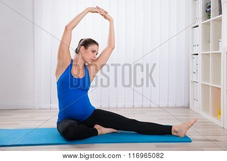 Pregnant Woman Stretching On Exercise Mat