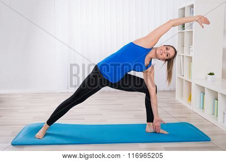 Young Female Stretching In Living Room