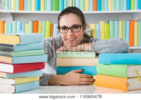 Woman Leaning On Books At Desk