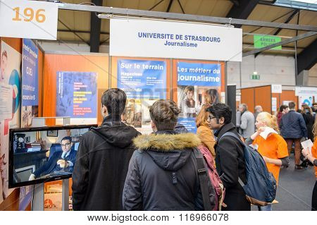 STRASBOURG FRANCE - FEB 4 2016: Children and teens of all ages attending annual Education Fair to choose career path and receive vocational counseling - Journalism stand
