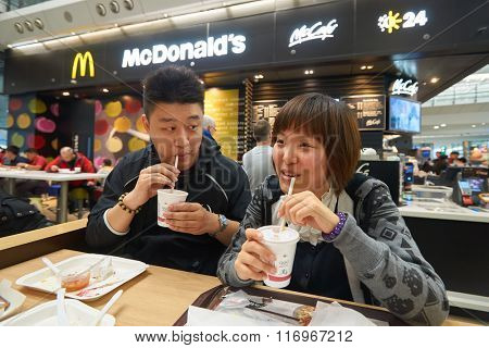 HONG KONG - JANUARY 29, 2016: people eat in McDonald's restaurant. McDonald's primarily sells hamburgers, cheeseburgers, chicken, french fries, breakfast items, soft drinks, milkshakes, and desserts